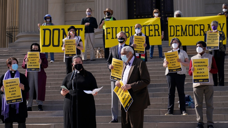 Rev. Liz Theoharis, centre left at microphone, co-director of The Poor People's Campaign, speak outside National City Christian Church in Washington, Monday, April 5, 2021. (AP Photo/Susan Walsh)