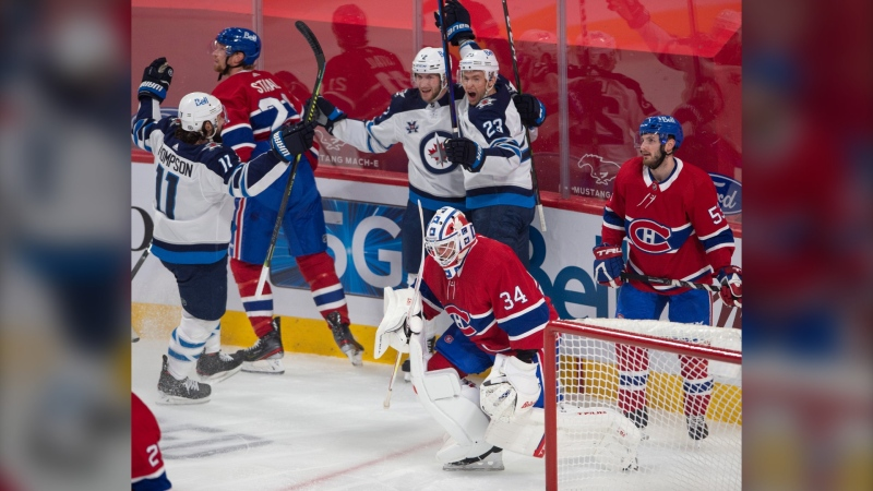 Winnipeg Jets centre Trevor Lewis (23) celebrates his goal with teammates Jansen Harkins (12) and Nate Thompson (11) as Montreal Canadiens goaltender Jake Allen (34), Eric Staal (12) and Victor Mete (53) look on during first period NHL hockey action Thursday, April 8, 2021 in Montreal. THE CANADIAN PRESS/Ryan Remiorz