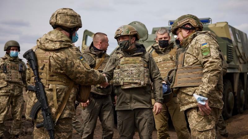 Ukrainian President Volodymyr Zelenskiy shakes hands woth a soldier as he visits the war-hit Donetsk region, eastern Ukraine, Thursday, April 8, 2021. (Ukrainian Presidential Press Office via AP)