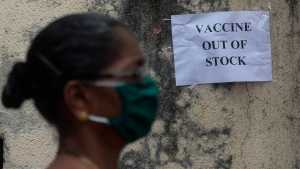 A woman wearing mask walks past a notice about the shortage of coronavirus (COVID-19) vaccine supply outside a vaccination centre in Mumbai, India, on April 8, 2021. (Rafiq Maqbool / AP)