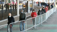 People wait in line at a COVID-19 vaccination clinic to receive the AstraZeneca vaccine at Olympic Stadium in Montreal, on Thursday, April 8, 2021. THE CANADIAN PRESS/Paul Chiasson