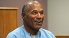 In this July 20, 2017, file photo, former NFL football star O.J. Simpson appears via video for his parole hearing at the Lovelock Correctional Center in Lovelock, Nev. Simpson and a Las Vegas hotel-casino have settled a lawsuit alleging that unnamed employees defamed Simpson by telling a celebrity news site he had been banned from the property in November 2017 for being drunk and disruptive. Simpson's attorney declined comment about the agreement. (Jason Bean/The Reno Gazette-Journal via AP, Pool, File)