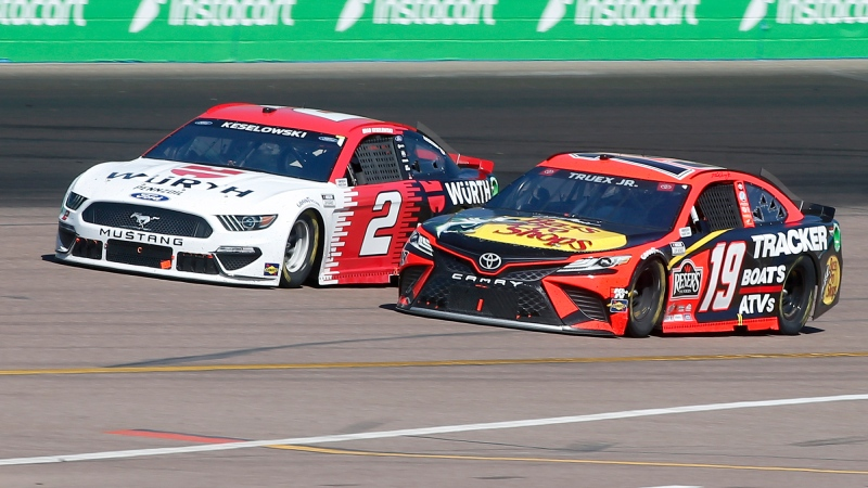 Martin Truex Jr (19) and Brad Keselowski (2) race out of Turn 2 during a NASCAR Cup Series auto race at Phoenix Raceway, Sunday, March 14, 2021, in Avondale, Ariz. (AP Photo/Ralph Freso)