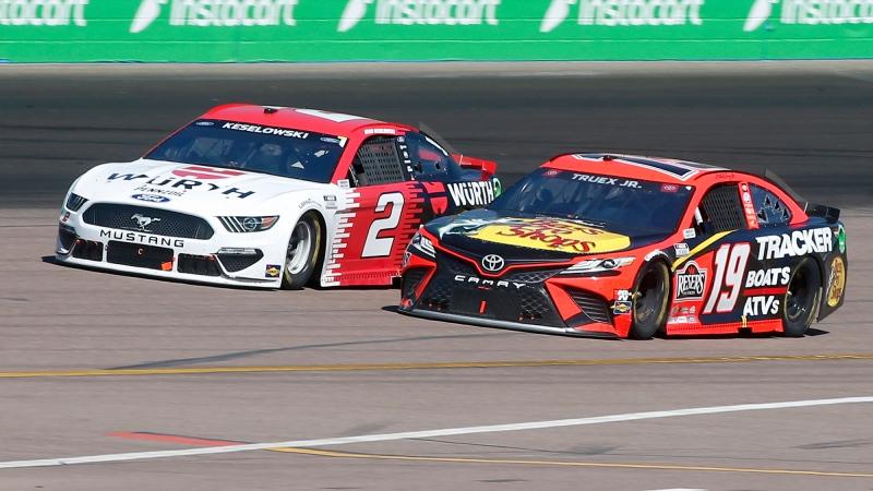 Martin Truex Jr (19) and Brad Keselowski (2) race out of Turn 2 during a NASCAR Cup Series auto race at Phoenix Raceway, Sunday, March 14, 2021, in Avondale, Ariz. (AP Photo/Ralph Freso)