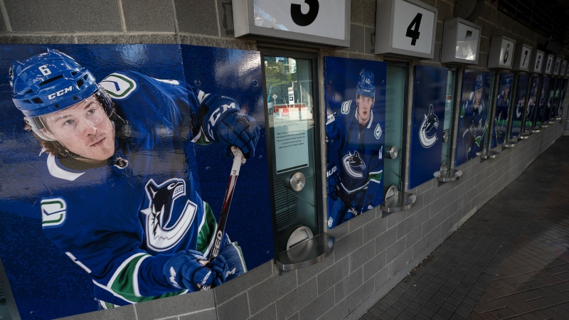 Photos of Vancouver Canucks players are pictured outside the closed box office of Rogers Arena in downtown Vancouver Thursday, April 8, 2021. (Jonathan Hayward / THE CANADIAN PRESS)