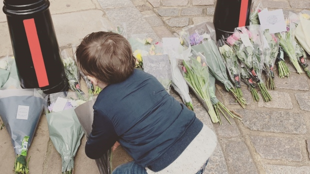 Four-year-old Matthew McEniry lays flowers at the entrance road to Windsor Castle in Windsor, England on Friday, April 9, 2021. (Source: Caitlin McEniry)