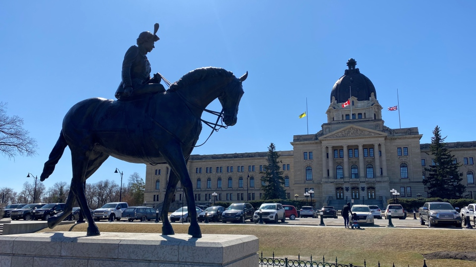Flags were lowered to half mast at the Saskatchewan Legislative Building on April 9, 2021, to mark the death of Prince Philip. A statue of Queen Elizabeth II is seen in the foreground. (Gareth Dillistone/CTV News)