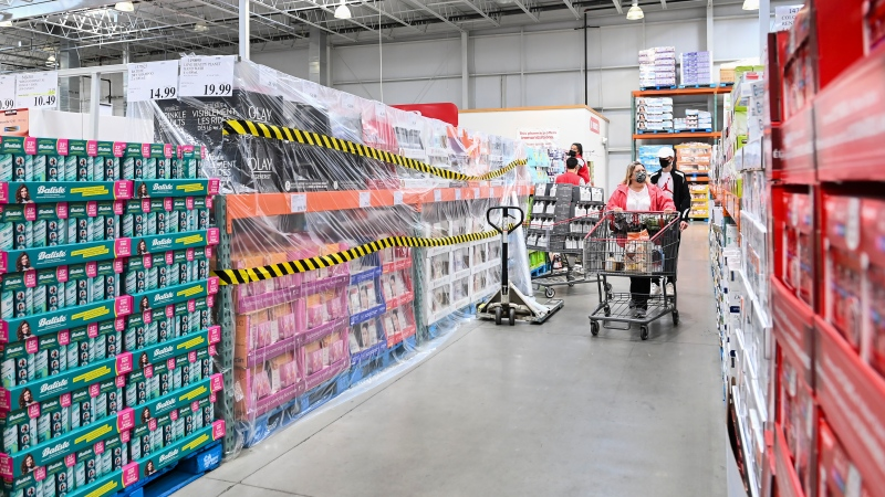 People shop for essential items only at Costco as the company was forced to block off aisles and sections that have been deemed non-essential during the COVID-19 pandemic in Mississauga, Ont., on Thursday, April 8, 2021. THE CANADIAN PRESS/Nathan Denette