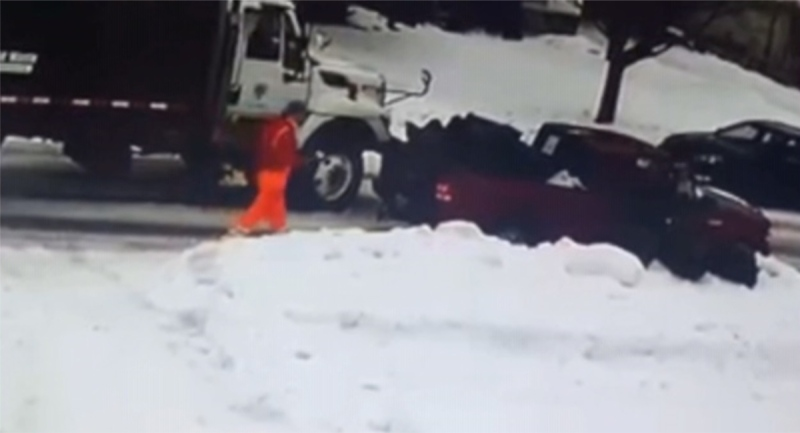 City workers confront a red pickup truck spotted dumping garbage in a London, Ont. neighbourhood in this image from surveillance video.