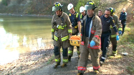 Rescue officials carry the female driver from the Humber River on Saturday, Nov. 7, 2009.