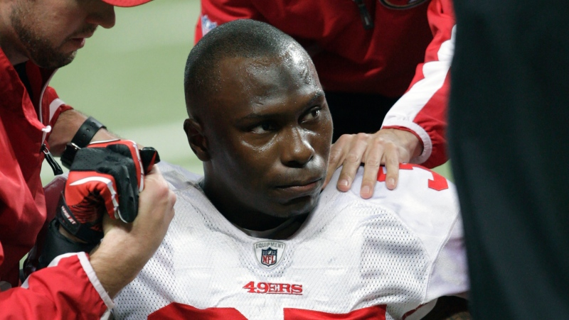 In this Dec. 26, 2010 file photo, San Francisco 49ers cornerback Phillip Adams (35) is attended to after injuring his left leg during the third quarter of an NFL football game against the St. Louis Rams, in St. Louis. (AP Photo/Tom Gannam, File)