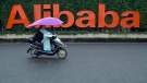 In this May 27, 2016, file photo, a woman rides a bike past the company logo outside the Alibaba Group headquarters in Hangzhou, in eastern China's Zhejiang province. (AP Photo/Ng Han Guan, File)