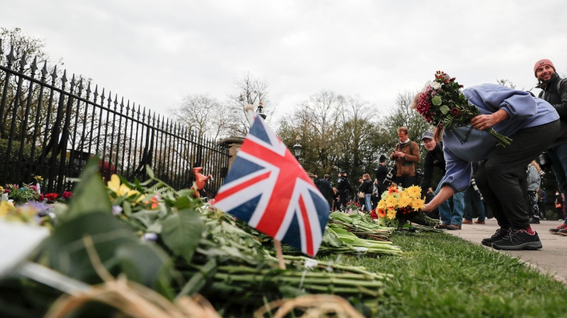 A member of the public lays flowers at the Cambridge gate of Windsor Castle in Windsor, England after the announcement regarding the death of Britain's Prince Philip, Friday, April 9, 2021. (AP / Frank Augstein)