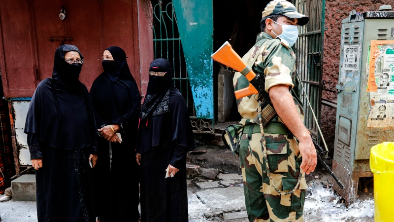 A paramilitary soldier stands guards as voters wait to cast their votes at a polling station during the fourth phase of West Bengal state elections in Kolkata, India, Saturday, April 10, 2021. (AP Photo/Bikas Das)