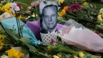 A photo of Britain's Prince Philip is among flowers left by the public outside the gates of Windsor Castle in Windsor, England, Saturday, April 10, 2021.  (AP Photo/Frank Augstein)