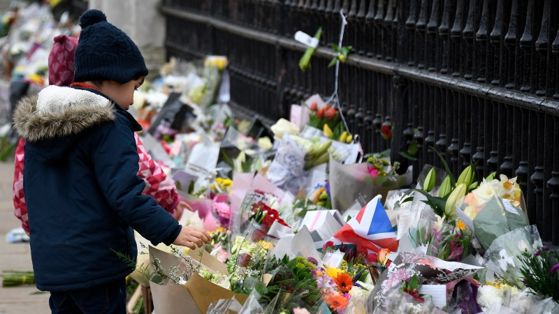 A child looks at flowers left outside the gates of Buckingham Palace in London, a day after the death of Prince Philip, Saturday, April 10, 2021. Prince Philip, the irascible and tough-minded husband of Queen Elizabeth II who spent more than seven decades supporting his wife in a role that mostly defined his life, died on Friday. (AP Photo/Alberto Pezzali)