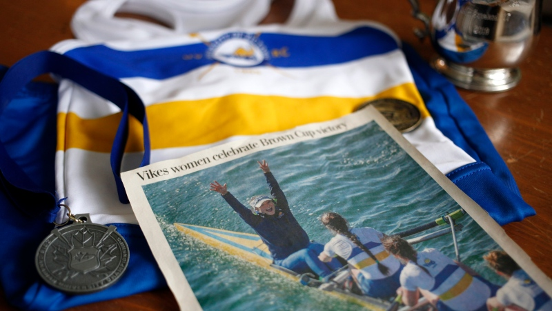 Former University of Victoria coxswain Lily Copeland shows off her national championship medals, uniform and celebratory newspaper clipping after winning the Brown Cup while being photographed at home in Brentwood Bay, B.C., on Saturday, November 16, 2019. THE CANADIAN PRESS/Chad Hipolito