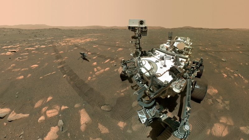 This Tuesday, April 6, 2021 image made available by NASA shows the Perseverance Mars rover, foreground, and the Ingenuity helicopter about 13 feet (3.9 metres) behind. This composite image was made by the WASTON camera on the rover's robotic arm on the 46th Martian day, or sol, of the mission. (NASA/JPL-Caltech/MSSS via AP)