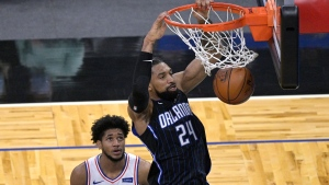 Orlando Magic center Khem Birch (24) dunks the ball in front of Philadelphia 76ers guard Isaiah Joe during the second half of an NBA basketball game, Thursday, Dec. 31, 2020, in Orlando, Fla. (AP Photo/Phelan M. Ebenhack)