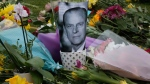 A photo of  Prince Philip is among flowers left by the public outside the gates of Windsor Castle, a day after the death of Prince Philip, in Windsor, England, Saturday, April 10, 2021. (AP / Frank Augstein)