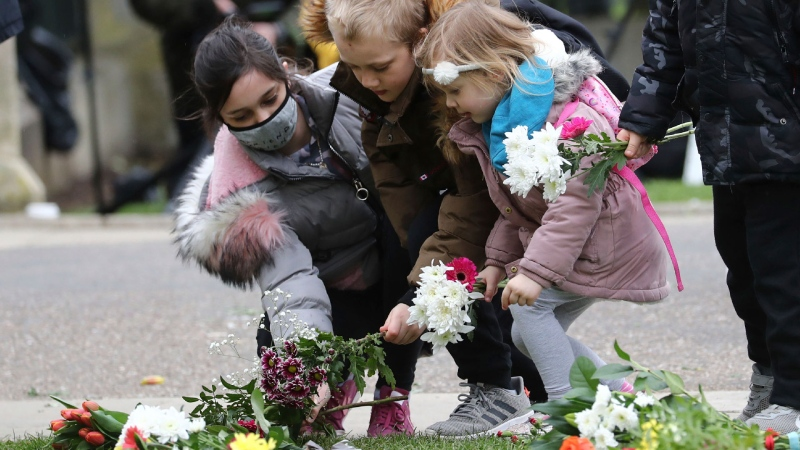 Children arrive to leave flowers at Cambridge Gate, at Windsor Castle, one day after the death of Prince Philip, in Windsor, England, Saturday, April 10, 2021.  (Gareth Fuller/PA via AP)