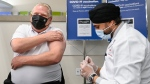 Ontario Premier Doug Ford, left, receives the Astrazeneca-Oxford COVID-19 vaccine from pharmacist Anmol Soor at Shoppers Drug Mart during the COVID-19 pandemic in Toronto on Friday, April 9, 2021. THE CANADIAN PRESS/Nathan Denette