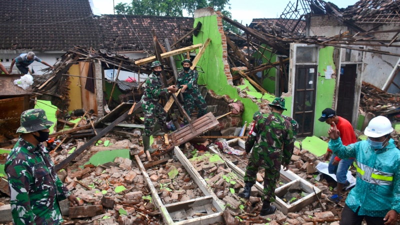 Indonesian soldiers help clear up rubble at a house damaged by an earthquake in Malang, East Java, Indonesia, Sunday, April 11, 2021. The deadly earthquake on Indonesia's main island of Java damaged multiple buildings, officials said Sunday. It didn't trigger a tsunami. (AP Photo/Hendra Permana)