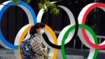 A woman wearing a protective mask to help curb the spread of the coronavirus walks in front of he Olympic Rings Tuesday, April 6, 2021, in Tokyo. Athletes at the Tokyo Olympics who come down with minor symptoms of COVID-19 could be isolated in a hotel lined up by local organizers of the games. (AP Photo/Eugene Hoshiko)