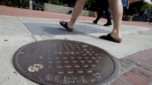 Pedestrians walk past a manhole cover for a sewer in Berkeley, Calif., Thursday, July 18, 2019.  (AP Photo/Jeff Chiu)