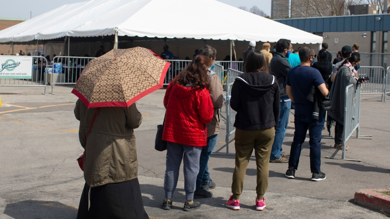 People queue up to receive the Moderna vaccine from staff from the Michael Garron Hospital at a mobile vaccination site outside the Masjid Mosque in Toronto on Saturday April 10, 2021. THE CANADIAN PRESS/Chris Young
