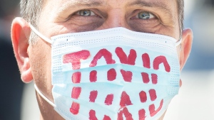 "A man wears a face mask reading ""Toxic"" during a demonstration in Montreal, Saturday, April 10, 2021, opposing the Quebec government's health and safety measures to curb the spread of COVID-19 in schools as the COVID-19 pandemic continues in Canada and around the world. THE CANADIAN PRESS/Graham Hughes"