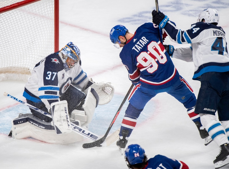 Montreal Canadiens' Tomas Tatar (90) moves in on Winnipeg Jets goaltender Connor Hellebuyck as Jets' Josh Morrissey defends during third period NHL hockey action in Montreal, Saturday, April 10, 2021. THE CANADIAN PRESS/Graham Hughes