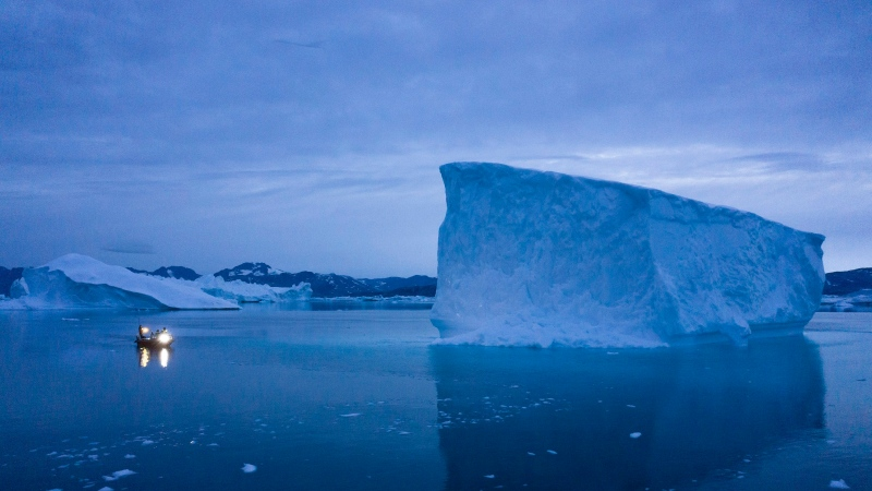FILE - In this Aug. 15, 2019, file photo, a boat navigates at night next to large icebergs in eastern Greenland. (AP Photo/Felipe Dana, File)