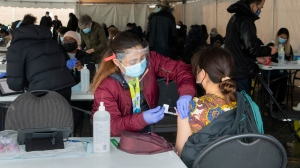 A nurse administers a COVID-19 vaccine at a pop-up clinic at the Masjid Darus Salaam in the Thorncliffe Park neighbourhood in Toronto on Sunday, April 11, 2021. Thousands of people have lined for vaccine doses at the mosque in the hard hit neighbourhood. THE CANADIAN PRESS/Frank Gunn