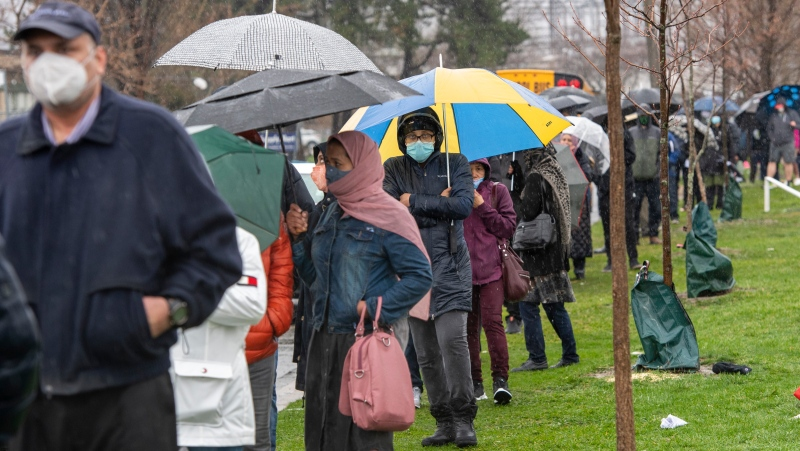 People line up in the rain for a COVID-19 vaccine at a pop-up clinic at the Masjid Darus Salaam in the Thorncliffe Park neighbourhood in Toronto on Sunday, April 11, 2021. Thousands of people have lined over the weekend for vaccine doses at the mosque in the hard hit neighbourhood. THE CANADIAN PRESS/Frank Gunn