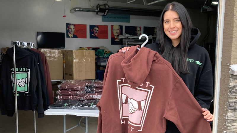 Brianne Helfrich proudly displays one of the hoodies her clothing company sells that directs 10 per cent of profits towards mental health charities (CTV News Edmonton/Brandon Lynch).