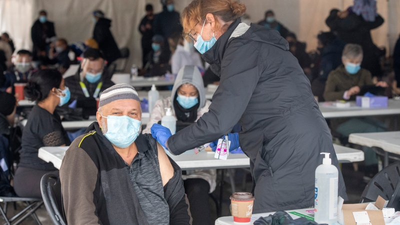 A nurse administers a COVID-19 vaccine at a pop-up clinic at the Masjid Darus Salaam in the Thorncliffe Park neighbourhood in Toronto on Sunday, April 11, 2021. Thousands of people have lined up over the weekend for vaccine doses at the mosque in the hard hit neighbourhood. THE CANADIAN PRESS/Frank Gunn