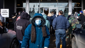 People line up outside a vaccine clinic as seniors wait to get the COVID-19 vaccine in Edmonton Alta, on Friday February 26, 2021 (The Canadian Press/Jason Franson).