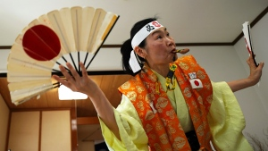 Olympic fan Kyoko Ishikawa shows her cheering at her home Saturday, April 10, 2021, in Tokyo. (AP Photo/Eugene Hoshiko)