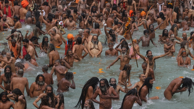 Devotees take holy dips in the Ganges River during Kumbh Mela, or pitcher festival, one of the most sacred pilgrimages in Hinduism, in Haridwar, northern state of Uttarakhand, India, Monday, April 12, 2021. Tens of thousands of Hindu devotees gathered by the Ganges River for special prayers Monday, many of them flouting social distancing practices as the coronavirus spreads in India with record speed. (AP Photo/Karma Sonam)