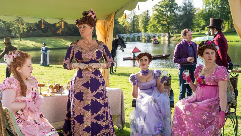 "This image released by Netflix shows Nicola Coughlan, from left, Polly Walker, Harriet Cains and Bessie Carter in a scene from ""Bridgerton."" Television producers Shonda Rhimes and Betsy Beers will be honored for their wardrobe efforts on projects like ""Grey's Anatomy"" and ""Bridgerton"" at the Costume Designers Guild Awards. (Liam Daniel/Netflix via AP)"