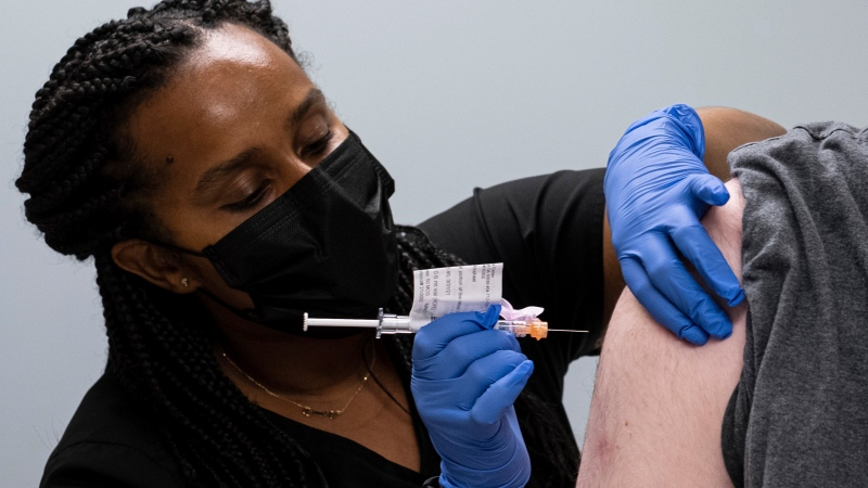 FILE - Cole Smith receives a Moderna variant vaccine shot from clinical research nurse Tigisty Girmay at Emory University's Hope Clinic, on Wednesday afternoon, March 31, 2021, in Decatur, Ga. (AP Photo/Ben Gray)