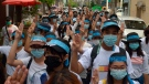 Anti-coup protesters flash the three-fingered salute while wearing headbands that read R2P, which means Responsibility to Protect, during a gathering in Ahlone township in Yangon, Myanmar Monday, April 12, 2021. (AP Photo)