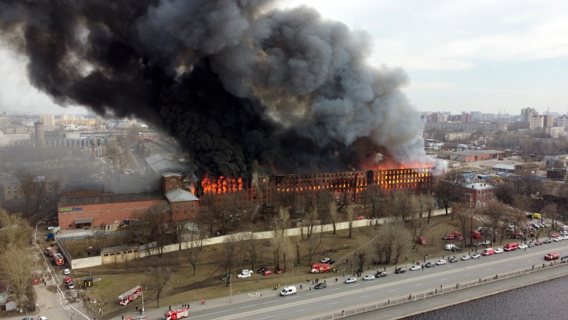 Smoke and flame rise from the Nevskaya Manufaktura textile factory, founded by English merchant J. Thornton in 1841, in St. Petersburg, Russia, Monday, April 12, 2021. The emergencies ministry said the fire had broken out over several floors of the red-brick Nevskaya Manufaktura building on the Oktyabrskaya Embankment of the Neva River. (AP Photo/Dmitri Lovetsky)