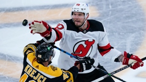 New Jersey Devils defenseman Dmitry Kulikov, right, redirects the puck while covered by Boston Bruins center David Krejci (46) during the first period of an NHL hockey game, Tuesday, March 30, 2021, in Boston. (AP Photo/Charles Krupa)