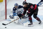 Ottawa Senators right wing Connor Brown tries to put the puck past Winnipeg Jets goaltender Connor Hellebuyck during second period NHL action Monday April 12, 2021 in Ottawa. (THE CANADIAN PRESS/Adrian Wyld)