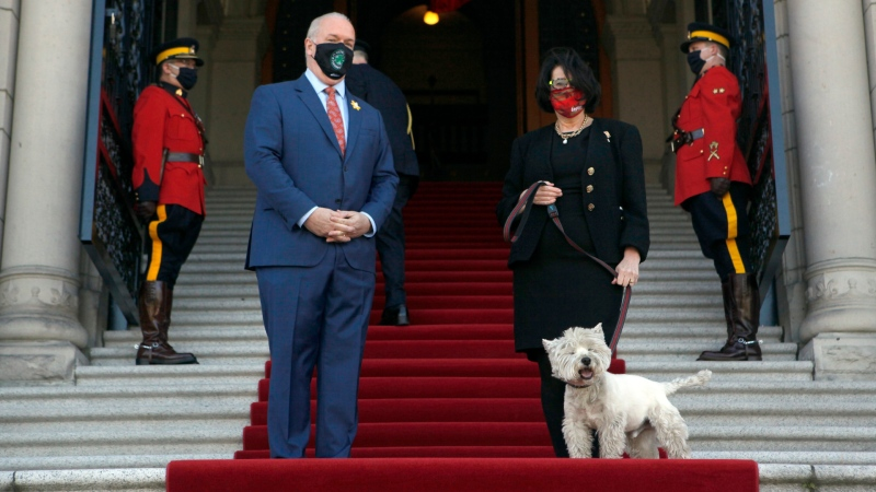 Premier John Horgan meets with Lt.- Gov. Janet Austin and her dog Macduff on the steps of B.C. Legislature before delivering the throne speech in Victoria, B.C., on April 12, 2021. (THE CANADIAN PRESS/Chad Hipolito)