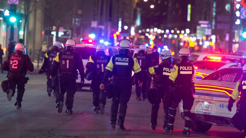 Police move down Saint Catherine street as anti-curfew protests continue for a second night Monday, April 12, 2021 in Montreal.THE CANADIAN PRESS/Ryan Remiorz