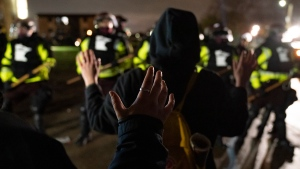 Demonstrators raise their hands while facing off against a perimeter of police as they defy an order to disperse during a protest against the police shooting of Daunte Wright, late Monday, April 12, 2021, in Brooklyn Center, Minn. (AP Photo/John Minchillo)