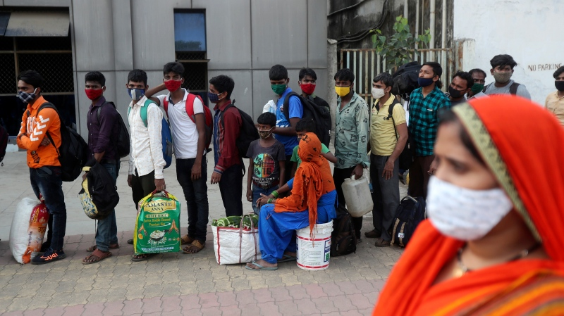 People wearing masks as a precaution against the coronavirus stand in a queue to board trains at Lokmanya Tilak Terminus in Mumbai, India, Sunday, April 12, 2021. (AP Photo/Rafiq Maqbool)